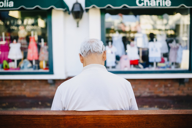 Lonely old man sitting on a bench