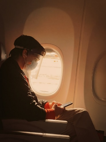 An elderly wearing a mask and face shield when traveling